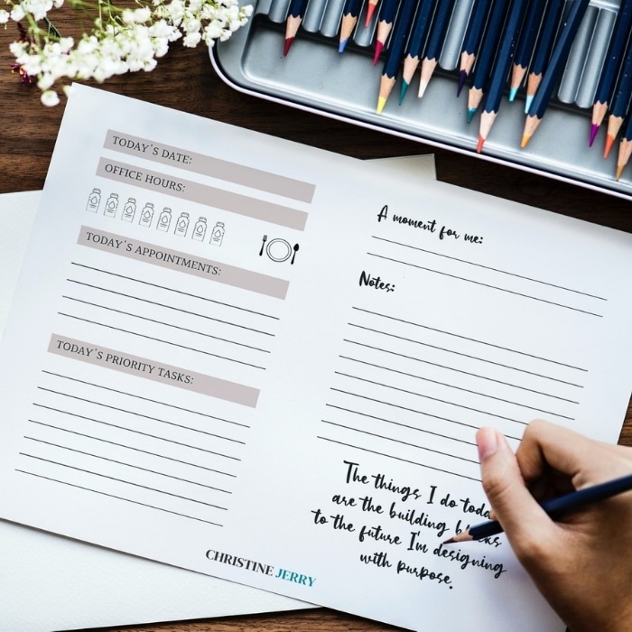 woman's hand writing on a planner page