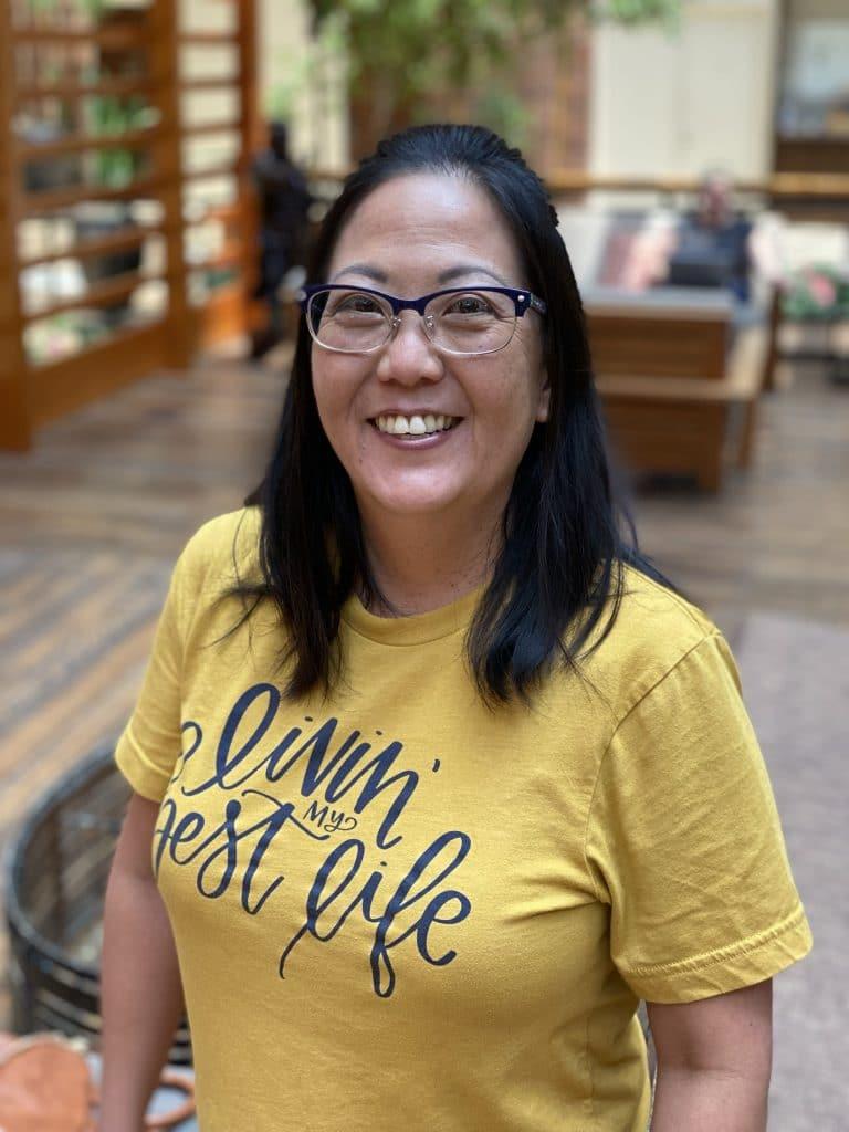 asian woman in hotel lobby wearing a yellow shirt